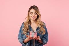 Mujer hermosa que presenta con el pequeño giftbox imagen de archivo libre de regalías