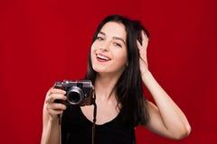 Mujer hermosa que presenta con la cámara retra en el fondo rojo Fotografía de archivo libre de regalías