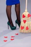 Mujer hermosa que presenta con los corazones rojos hechos del papel en el bro Fotografía de archivo
