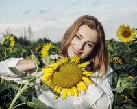 Mujer hermosa que presenta en campo, belleza y naturaleza del girasol Fotos de archivo libres de regalías
