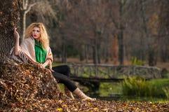Mujer hermosa que presenta en parque durante la estación del otoño. Muchacha rubia que lleva la blusa verde y la presentación gran Foto de archivo