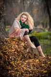 Mujer hermosa que presenta en parque durante la estación del otoño. Muchacha rubia que lleva la blusa verde y la presentación gran Fotos de archivo