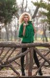 Mujer hermosa que presenta en parque durante la estación del otoño. Muchacha rubia que lleva la presentación verde de la blusa al  Foto de archivo
