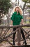 Mujer hermosa que presenta en parque durante la estación del otoño. Muchacha rubia que lleva la presentación verde de la blusa al  Fotos de archivo libres de regalías