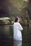 Mujer hermosa que presenta en una corriente de la montaña Fotografía de archivo