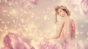 Mujer hermosa que presenta en una fantasía rosada de la peonía Imagen de archivo libre de regalías