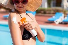 Mujer hermosa que protege su piel contra la quemadura, aplicando la loción del sol en su hombro por la piscina Factor de protecci fotos de archivo