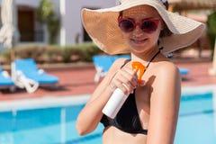 Mujer hermosa que protege su piel contra la quemadura, aplicando la loci?n del sol en su hombro por la piscina Factor de protecci imagenes de archivo