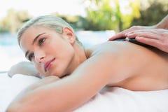 Mujer hermosa que recibe el masaje de piedra en la granja de salud Imagen de archivo libre de regalías