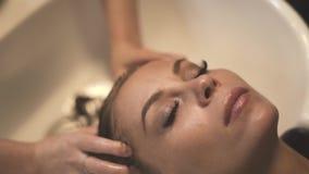 Mujer hermosa que recibe el masaje principal mientras que lava el pelo en cierre del salón del balneario encima del peluquero que