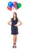 Mujer hermosa que retiene los globos detrás de ella Imagen de archivo