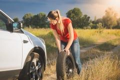 Mujer hermosa que rueda el neumático de repuesto para cambiar el plano Fotografía de archivo
