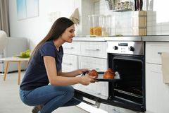 Mujer hermosa que saca la bandeja de bollos cocidos del horno imagenes de archivo