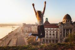 Mujer hermosa que salta enfrente de fachada y de la entrada famosas al hotel Gellert en los bancos de Danubio en Budapest, Hungrí imagenes de archivo