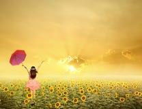 Mujer hermosa que salta y que sostiene el paraguas rojo i Fotos de archivo