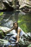 Mujer hermosa que se baña en la corriente cerca de la cascada Fotografía de archivo libre de regalías