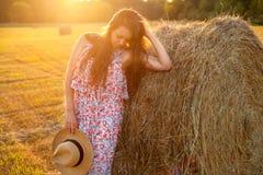 Mujer hermosa que se coloca cerca de una bala de heno en campo Fotografía de archivo libre de regalías