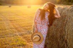 Mujer hermosa que se coloca cerca de una bala de heno en campo Imagen de archivo libre de regalías