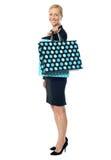Mujer hermosa que se coloca con el bolso de compras Fotos de archivo libres de regalías