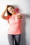 Mujer hermosa que se coloca con un caramelo rojo del corazón en las manos Imagen de archivo libre de regalías