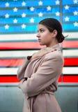 Mujer hermosa que se coloca delante de bandera americana y que mira al lado Concepto del patriotismo de la nación de la gente foto de archivo libre de regalías