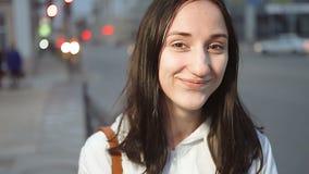 Mujer hermosa que se coloca delante de la calle de la ciudad de la noche con la luz y la sonrisa móviles de los coches almacen de metraje de vídeo