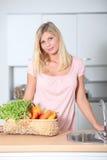 Mujer hermosa que se coloca en cocina Imagen de archivo