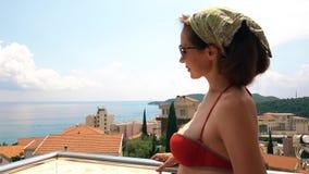 Mujer hermosa que se coloca en la terraza del seaview en un día de verano almacen de video