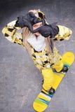 Mujer hermosa que se coloca en snowboard Foto de archivo libre de regalías