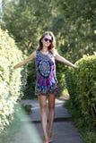 Mujer hermosa que se coloca en un vestido brillante entre los arbustos Fotos de archivo