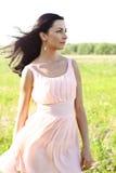 Mujer hermosa que se coloca en un vestido del rosa del campo, estilo de la moda, el concepto de retrato al aire libre Fotografía de archivo libre de regalías