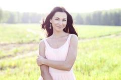 Mujer hermosa que se coloca en un vestido del rosa del campo, estilo de la moda, el concepto de retrato al aire libre Fotografía de archivo