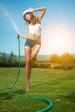Mujer hermosa que se divierte en jardín del verano con el jardín ho imagen de archivo