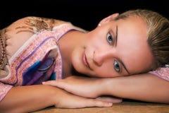 Mujer hermosa que se reclina sobre sus brazos y pensamiento Imagen de archivo libre de regalías