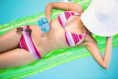 Mujer hermosa que se relaja en cama de aire en poo de la natación Foto de archivo