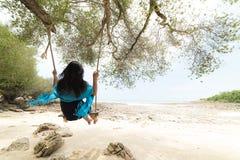Mujer hermosa que se relaja en el oscilación de madera debajo de árbol fotos de archivo