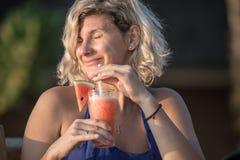 Mujer hermosa que se relaja en el restaurante de la playa Imágenes de archivo libres de regalías