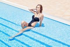Mujer hermosa que se relaja en la piscina. En agua en verano. Imágenes de archivo libres de regalías