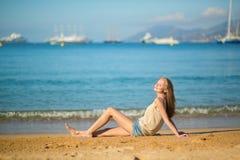 Mujer hermosa que se relaja en la playa Imagenes de archivo