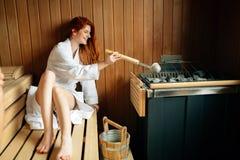 Mujer hermosa que se relaja en sauna finlandesa Foto de archivo