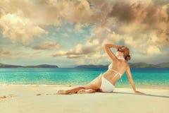 Mujer hermosa que se relaja en una playa arenosa blanca soleada. Imagen de archivo