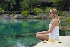 Mujer hermosa que se relaja y que medita en una piscina de la selva foto de archivo libre de regalías