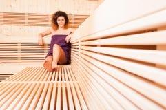 Mujer hermosa que se relaja y que sonríe en una sauna de madera Fotos de archivo libres de regalías