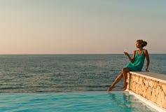 Mujer hermosa que se sienta cerca de piscina del infinito Imágenes de archivo libres de regalías