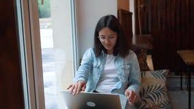 Mujer hermosa que se sienta con el red-libro portátil en barra moderna del café, freelancer de sexo femenino encantador joven almacen de video