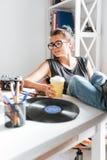 Mujer hermosa que se sienta con las piernas en la tabla y el café de consumición Foto de archivo libre de regalías