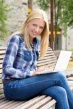 Mujer hermosa que se sienta en banco en parque con el ordenador portátil Foto de archivo libre de regalías