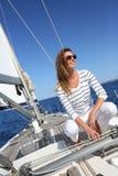 Mujer hermosa que se sienta en cubierta de la navegación Imágenes de archivo libres de regalías