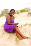 Mujer hermosa que se sienta en dunas de arena imagen de archivo