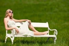 Mujer hermosa que se sienta en el banco blanco Imagen de archivo